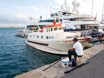 Fisherman sitting at the port Stock Images