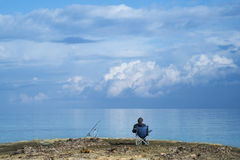 Fisherman sitting relaxed with a blue sky Royalty Free Stock Photos
