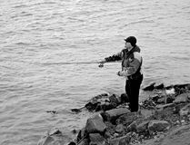 Fisherman sitting by the river fishing Stock Images