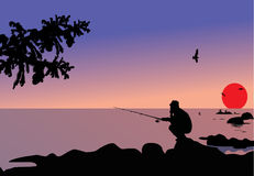 Fisherman sitting on stone Royalty Free Stock Image