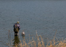 fisherman sitting in the water of rivers, lakes, sea stock photos