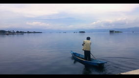 Fisherman in a small boat with his traps on the bi stock video footage