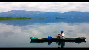 Fisherman in a small boat with his traps on the bi stock footage
