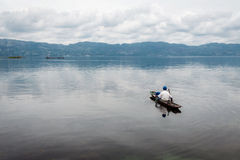 Fisherman in a small boat with his traps on the biggest lake in Royalty Free Stock Photography