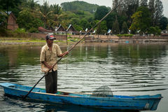 Fisherman in a small boat with his traps on the biggest lake in Royalty Free Stock Photo