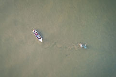 Fisherman with small boat in the sea. Aerial view from flying dr Stock Images