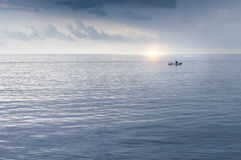 Fisherman in a small boat at sea Royalty Free Stock Photography