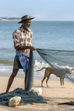 A fisherman sorting a fishing net on Arugam Bay beach in the early morning. Stock Images