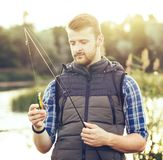 Fisherman with a spinning and bait catching fish on a lake or river. Man on a weekend with a fishing road. Hobby and royalty free stock images