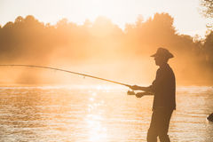 Fisherman with spinning. At lake on sunset Stock Photos