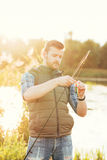 Fisherman with a spinning rod and bait Stock Images