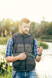 Fisherman with a spinning rod and bait Royalty Free Stock Photography