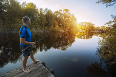 Fisherman with a spinning rod catching fish on a river. Royalty Free Stock Photography