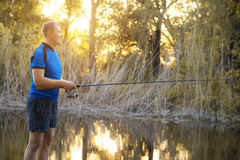 Fisherman with a spinning rod catching fish on a river. Stock Images