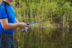 Fisherman with a spinning rod catching fish on a river. Royalty Free Stock Photo