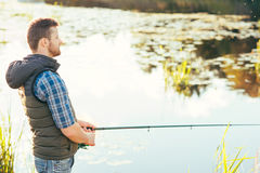 Fisherman with a spinning rod catching fish in a river Royalty Free Stock Images