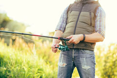 Fisherman with a spinning rod catching fish in a river Stock Photos