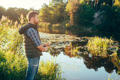 Fisherman with a spinning rod catching fish in a river Royalty Free Stock Photo