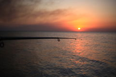 Fisherman sport hobby fishing rod or spinning reel. On sea beach during sunset Stock Images
