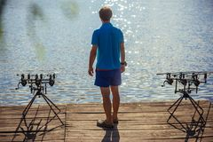 Fisherman stand on wooden pier, back view. Man fishing with spinning rods, reels at lake water. Summer vacation, adventure, activity. Fishing, angling, hobby stock image