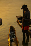 Rewards. Fisherman standing boat African lake Royalty Free Stock Photography