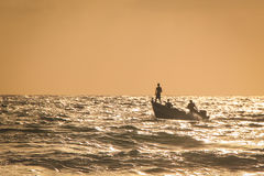 Fisherman standing on a boat at sea sunset royalty free stock image