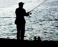 Fisherman standing on edge of dock with fishing rod near river. In city Stock Images