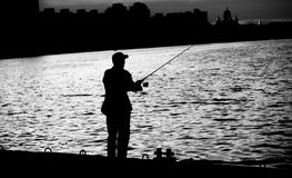 Fisherman standing on edge of dock with fishing rod near river in city Stock Images
