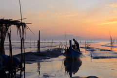 Fisherman is standing on fishing boat with sunrise background. At thailand Stock Photos