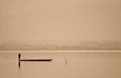 Fisherman are standing for fishing in lake. In sepia color Royalty Free Stock Image