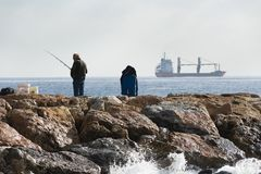 A fisherman standing with the fishing rod in his hand, he is on royalty free stock photos