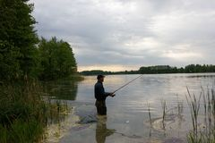 Fisherman. Standing in the lake and catching the fish on cloudy day stock photo