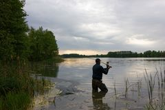 Fisherman. Standing in the lake and catching the fish at cloudy day stock photo