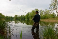 Fisherman. Standing in the lake and catching the fish at cloudy day Stock Image