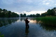 Fisherman. Standing in the lake and catching the fish during sunrise Stock Photo