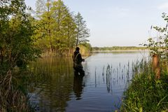 Fisherman. Standing in lake with fishing rod Royalty Free Stock Images