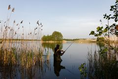 Fisherman. Standing in lake with fishing rod Royalty Free Stock Photos