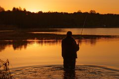 Fisherman. Standing in the Lake at Sunset Royalty Free Stock Photography