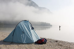 Fisherman standing in a mountain lake Stock Images