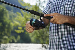 Fisherman standing near river and holding fishing rod royalty free stock photos