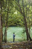 Fisherman standing near river and holding fishing rod Stock Photos