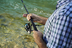 Fisherman standing near river and holding fishing rod royalty free stock photography