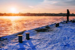 Fisherman standing on a pier at dawn sky background with sun rays and reflected in the sea water. Stock Photos