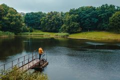 Fisherman standing on pier of the lake and fishing on rainy day stock photo
