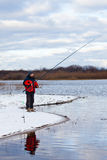 Fisherman standing on the river with fishing rod stock photo