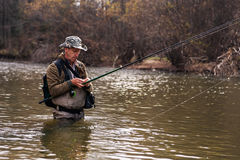 Fisherman standing in river when fishing for trout Royalty Free Stock Photos