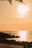 Fisherman standing on rock under sunset light Stock Image