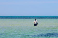 Fisherman standing in the sea Royalty Free Stock Photo