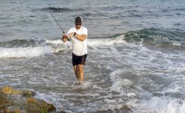 Fisherman standing at the seashore hooks a fish. Fisherman standing at the seashore hooks a fish: Rock fishing with stickbait. action active adventure angler stock photo