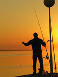 A fisherman standing by the sunset Royalty Free Stock Photo